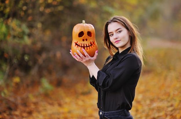 Attraente giovane donna tiene jacks lantern