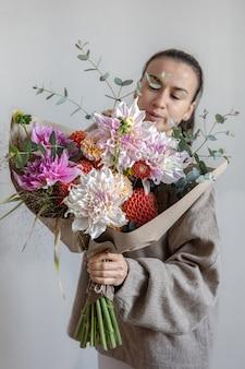 Una giovane donna attraente tiene in mano un grande bouquet festivo con crisantemi e altri fiori.