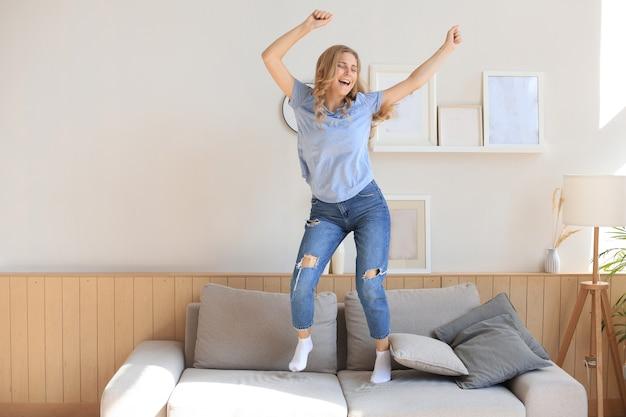 Attraente giovane donna si diverte a casa. la ragazza sta saltando e ballando sul divano.