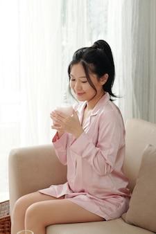 Attraente giovane donna in pigiama rosa chiaro che si gode l'odore della crema idratante che sta per applicare
