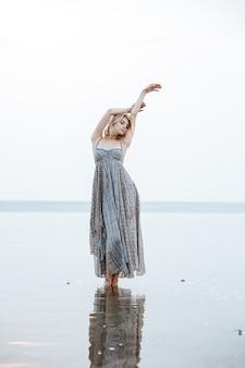 Attraente giovane donna in abito lungo in piedi nel lago