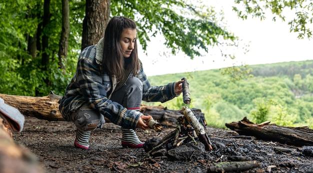 Una giovane donna attraente accende un fuoco per scaldarsi nella foresta