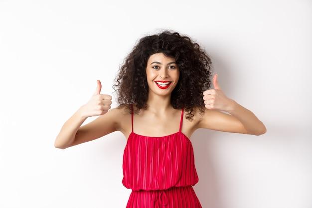 Attraente giovane donna che consiglia l'offerta promozionale, mostrando il pollice in su e sorridente, come il prodotto, in piedi in abito rosso festivo su sfondo bianco.