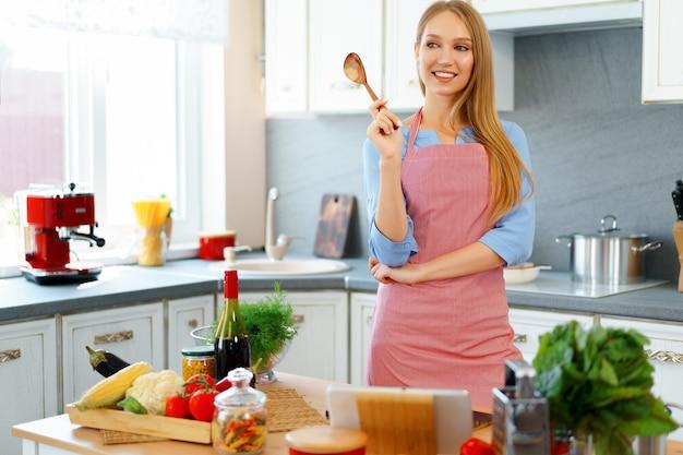 Attraente giovane donna in grembiule rosso in piedi nella sua cucina