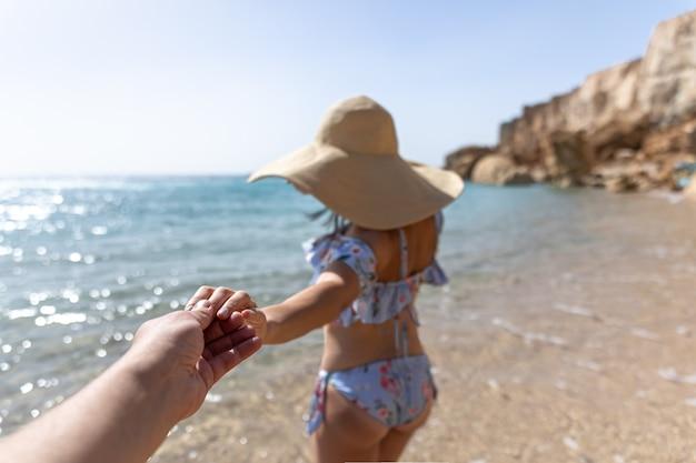 Una giovane donna attraente in riva al mare in costume da bagno e un grande cappello cammina per mano con un ragazzo.