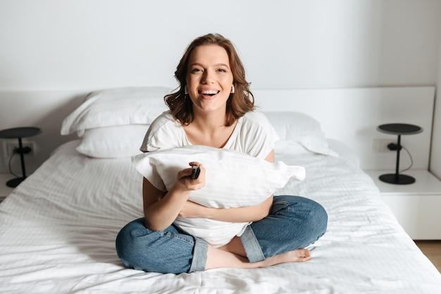 Attraente giovane donna seduta sul letto a casa a guardare la tv, ridendo