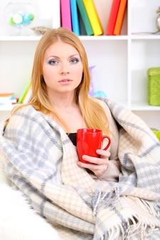 Attraente giovane donna seduta sul divano, che tiene in mano una tazza con una bevanda calda, sullo sfondo dell'interno della casa
