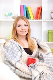 Attraente giovane donna seduta sul divano, che tiene in mano una tazza con una bevanda calda