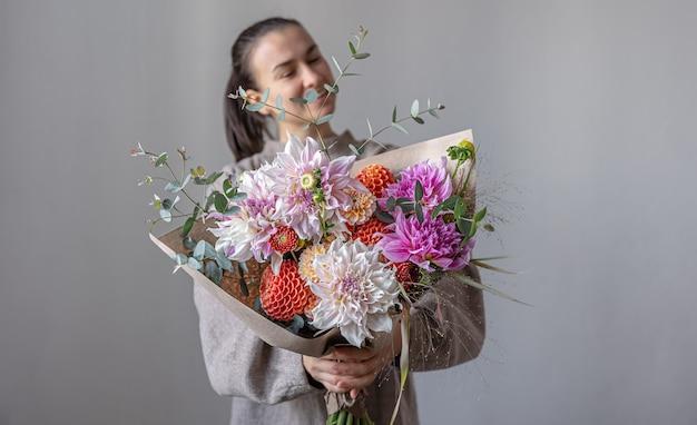 Una giovane donna attraente sorride e tiene in mano un grande bouquet festivo con crisantemi e altri fiori.