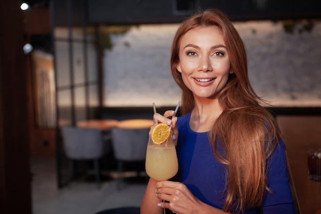 Attraente giovane donna che sorride alla macchina fotografica, tenendo il suo drink, godendo la serata al bar