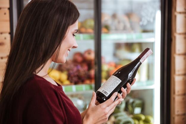 Attraente giovane donna in piedi e scegliendo il vino nel negozio di alimentari