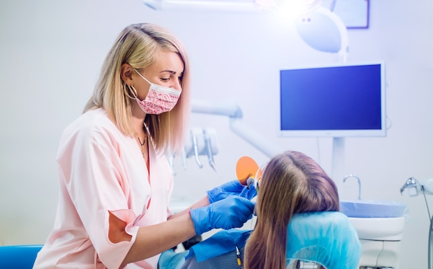 Attraente giovane donna in stomatologia clinica con allegro dentista femminile.