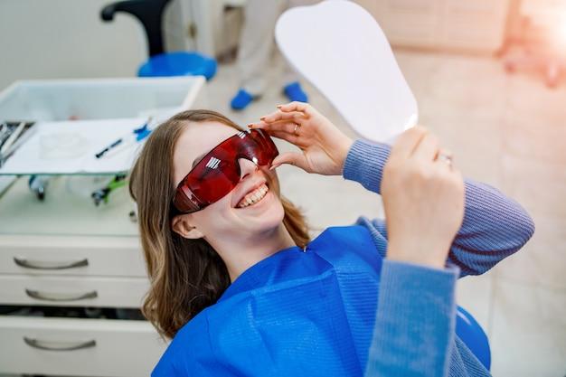 La giovane donna attraente in stomatologia sta guardando il suo nuovo brillante odore. concetto di denti sani.
