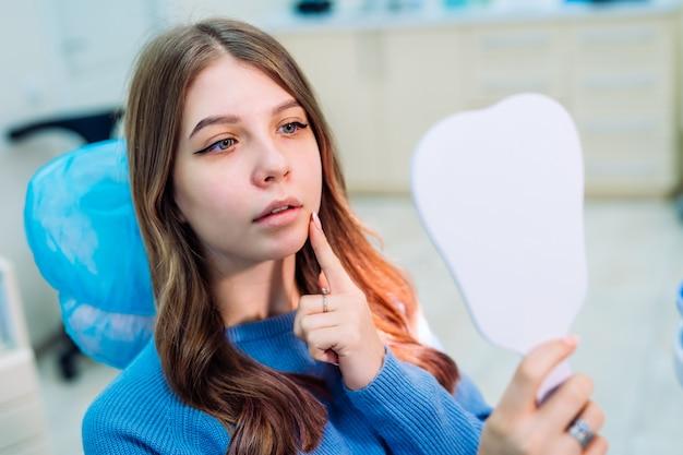 La giovane donna attraente in stomatologia sta guardando il mirrow. concetto di denti sani.