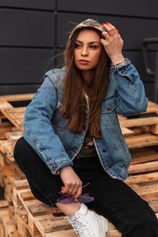La giovane donna attraente in vestiti casuali alla moda mette il cappuccio militare sulla testa all'aperto. la ragazza hipster alla moda americana in jeans giovanili indossa stivali bianchi alla moda seduti su tavole di legno vicino al muro.