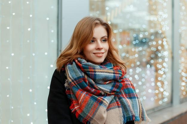Attraente giovane donna in un elegante cappotto invernale nero con una sciarpa calda alla moda di lana si trova nella città vicino alla finestra decorata con luci festive. ragazza felice che cammina in città