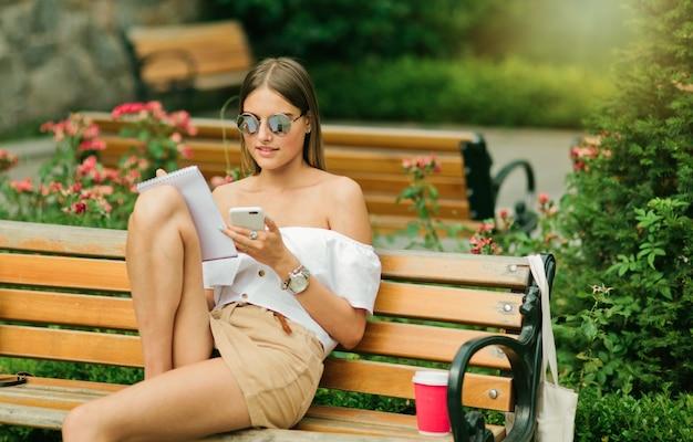 Attraente giovane donna in abiti estivi e occhiali da sole tenendo smartphon