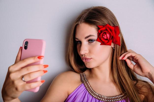 Attraente giovane donna prende un selfie sul suo smartphone, imbronciato le labbra e raddrizzandosi i capelli con un fiore di rosa rossa.