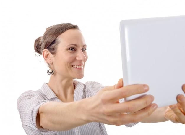 Giovane donna attraente che prende selfie con la compressa in uno studio