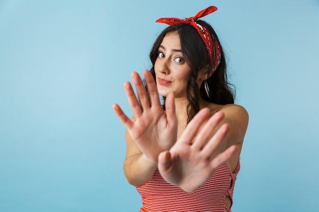 Attraente giovane donna che indossa abiti estivi in piedi isolato su blu, mani tese