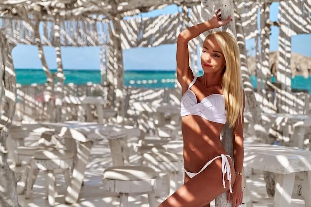 Attraente giovane donna che indossa il costume da bagno in piedi sul muro di bambù bianco