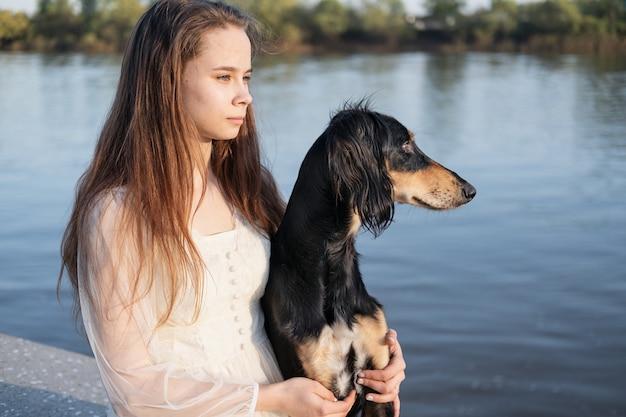 Attraente giovane donna in abito bianco che tiene cane saluki. guarda in una direzione. levriero persiano. concetto di cura degli animali domestici. amore e amicizia tra uomo e animale.