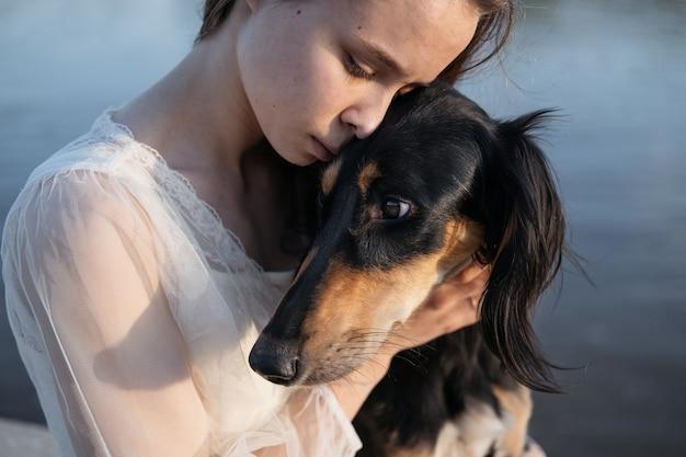 Attraente giovane donna in abito bianco che tiene il viso di cani saluki con amore. faccia a faccia. levriero persiano. concetto di cura degli animali domestici. amore e amicizia tra uomo e animale.
