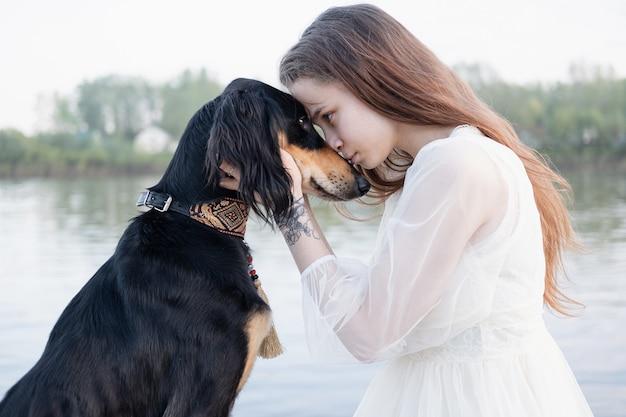 Attraente giovane donna in abito bianco che tiene la faccia di cani saluki