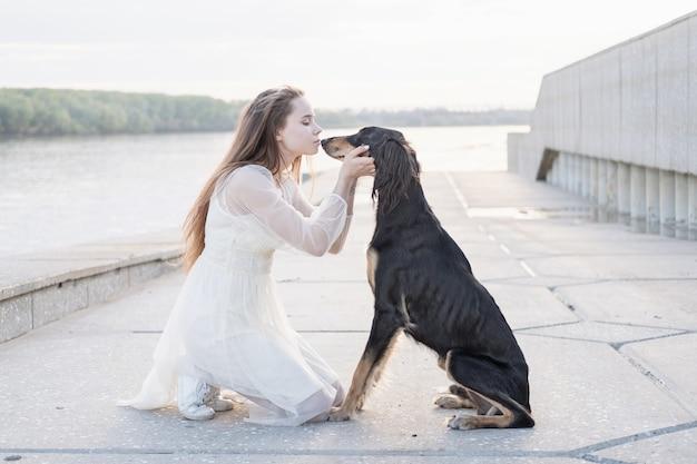 Attraente giovane donna in abito bianco seduto bacio saluki dog