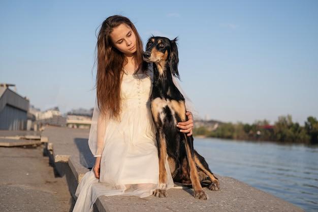 Attraente giovane donna in abito bianco seduta con saluki dog