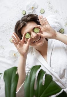Attraente giovane donna in una veste bianca si trova in un salone spa, fette di cetriolo fresco, vista dall'alto.