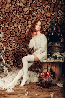 Attraente giovane donna in un colpo di moda invernale indossa un maglione di lana bianco e calzini lavorati a maglia. capodanno e natale.