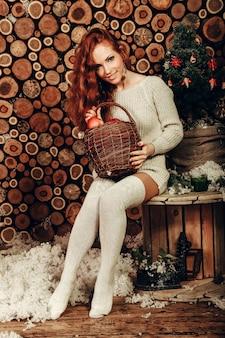La giovane donna attraente in un modo dell'inverno ha sparato indossando un maglione di lana bianco e calzini lavorati a maglia