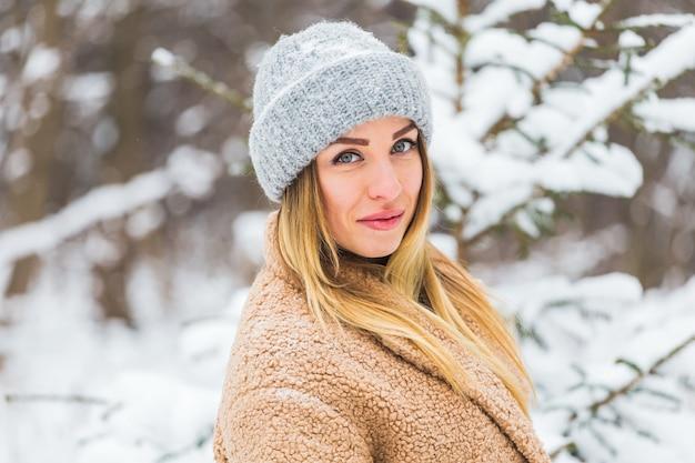 Attraente giovane donna nell'orario invernale all'aperto. concetto di neve, vacanze e stagione.
