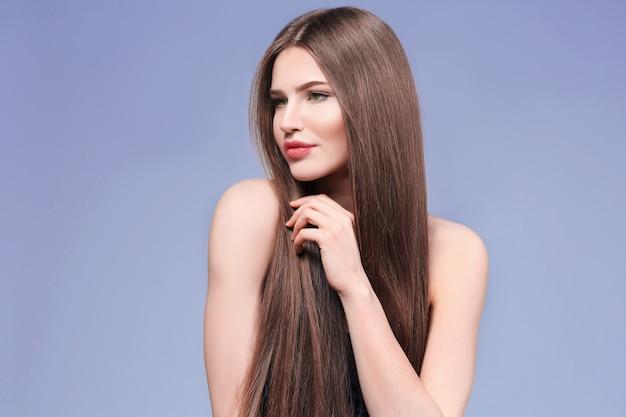 Attraente giovane donna con bei capelli lunghi su sfondo chiaro