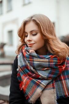 Attraente giovane donna con un bel sorriso con i capelli ricci in un cappotto caldo alla moda con una sciarpa di lana vintage all'aperto contro un edificio bianco. la bella ragazza gode del giorno di autunno.