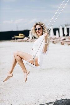 Attraente giovane donna con capelli biondi ricci seduto sull'altalena mentre si rilassa sulla spiaggia sabbiosa vicino al lago. bella donna che indossa occhiali da sole alla moda ed elegante costume da bagno bianco.