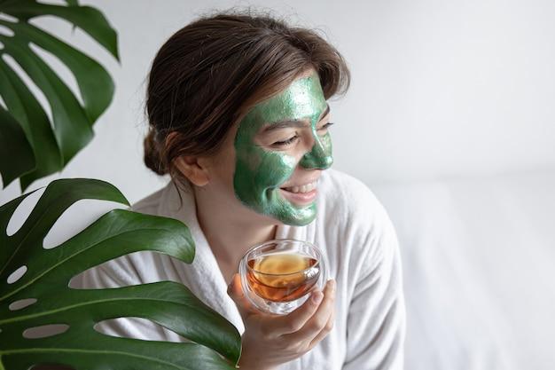 Attraente giovane donna con una maschera cosmetica verde sul viso e in una veste bianca con tè in mano, il concetto di procedure termali.