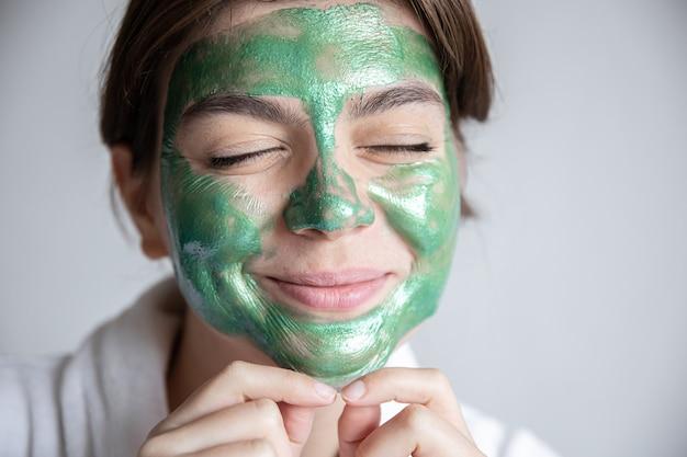Attraente giovane donna con una maschera cosmetica verde sul viso e in una veste bianca