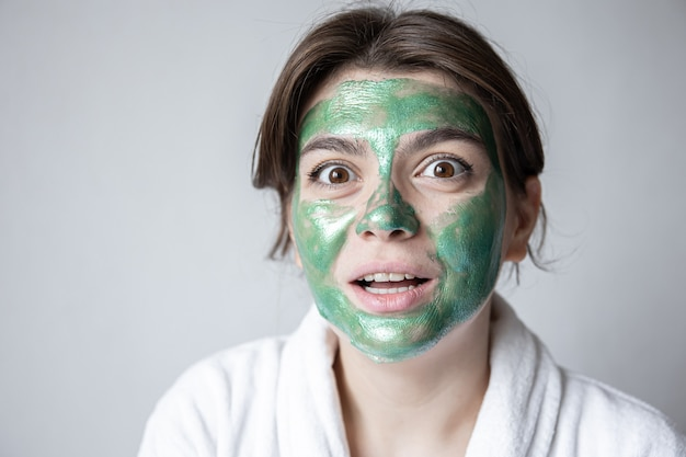 Attraente giovane donna con una maschera cosmetica verde sul viso