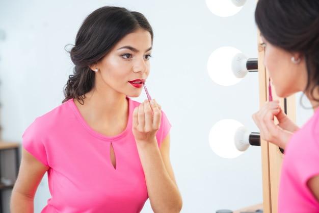 Attraente giovane donna con pennello per labbra guardando lo specchio e applicando rossetto rosso alle labbra