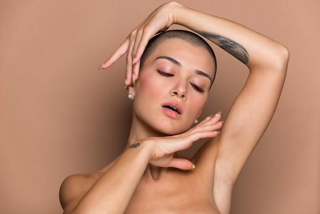 Attraente giovane donna con i capelli corti in posa sul beige