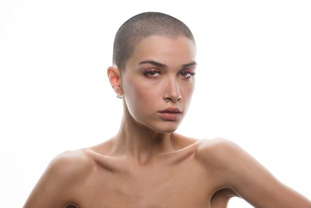 Attraente giovane donna con i capelli corti in posa su bianco