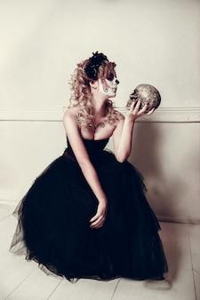 Giovane donna attraente con trucco del cranio dello zucchero. giorno messicano della donna morta che indossa trucco teschio di zucchero e corona di fiori.