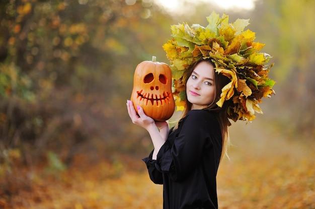 Una giovane donna attraente con una ghirlanda di foglie autunnali sulla testa tiene in mano la lanterna di jack Foto Premium