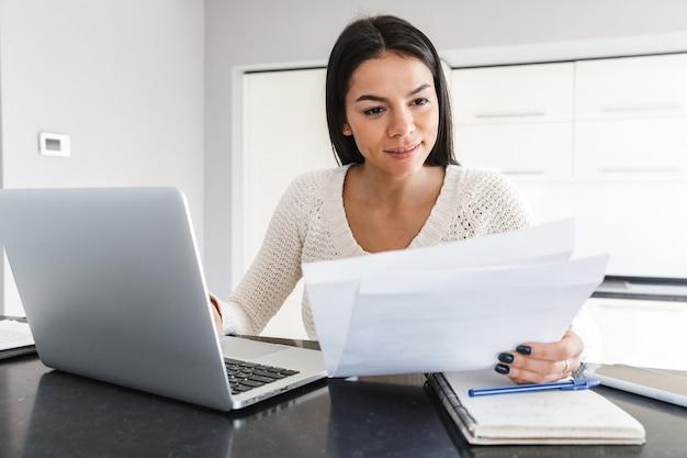 Attraente giovane donna che lavora con computer portatile e documenti mentre è seduta in cucina