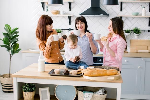 Le giovani donne attraenti, la donna di mezza età e la piccola figlia carina stanno cucinando sulla cucina. famiglia amorosa che mangia i loro muffin nella cucina e che beve caffè