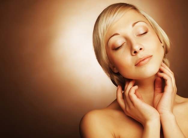 Attraenti giovani donne con i capelli d'oro su sfondo beige