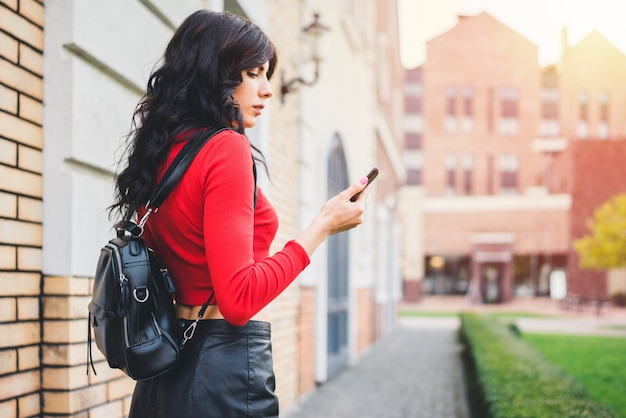 Attraente ragazza turistica dai capelli scuri che cammina per la strada della città vecchia con il cellulare in mano, navigando nell'applicazione mappa