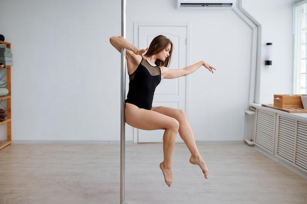 Attraente donna in pole dance allenamento in classe. le ragazze con un corpo perfetto mostrano uno stretching eccellente